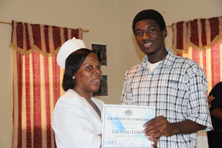 (L-R) Charlestown Secondary School student Mr. Luchano Lewis one of the 50 interns receives his certificate of completion in the 8th Annual Summer Job Attachment Programme from Health Services Coordinator and Head Nurse at the Alexandra Hospital Mrs. Aldris Pemberton