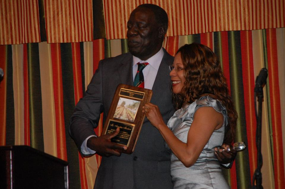 Mr. Augustine Merchant receiving  award from Mrs. Juliet Maynard Webster