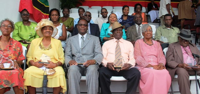 (Front row; left to right) Awardees Ms. Deloris Clarke, Ms. Violet Lake, Mr. Joseph Wiltshire, Mr. Reuben Williams, Mr. and Mrs. Evan Jeffers. (Middle row; left to right) Mrs. Lorette Brand-Willett on behalf of the late Mr. Hubert Brand, Ms. Tazel Liburd on behalf of Mr. Emeale Liburd, Mr. Herman Liburd, Mrs. Sonita Daniel, Mr. Arville Cornelius, Mr. Javel Cornelius on behalf of Mr. Trevor Cornelius. (Back row; left to right) Ms. Hilarena Liburd, Mrs. Cavelle Jeffers, Mr. Earl Hanley Jr. and Ms. Alicia Hanley on behalf of the late Mr. Earl Hanley. Absent was Mr. Andy Liburd