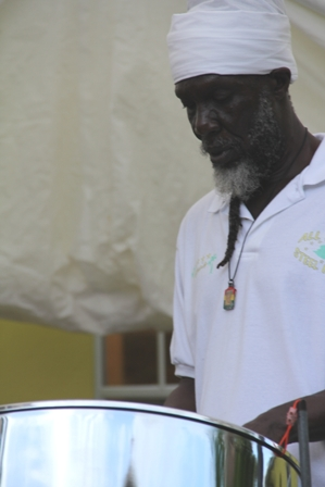 Musician and Villager Baba Tungi playing the national anthem on his steel pan