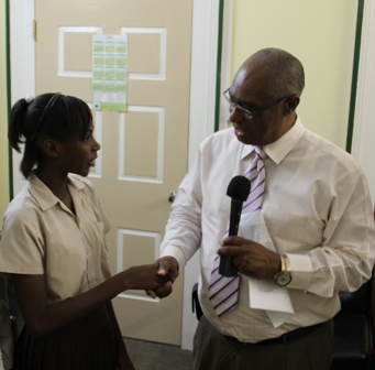 "Premier of Nevis, Hon. Joseph Parry commending Nevis Tourism ""Junior Minister"", Miss Clayticia Daniel."