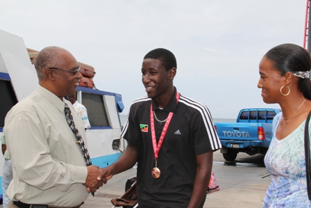 Premier of Nevis welcomes Nevis' Bronze winning medallist at the Commonwealth Youth Games in the Island of Man Mr. Adrian Williams home while his mother Ms. Glenett Williams looks on