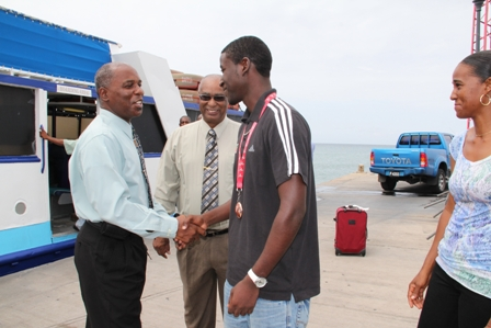 Permanent Secretary in the Ministry of Youth and Sports on Nevis Mr. Alsted Pemberton welcomes Nevisian Athlete Adrian Williams on his return to Nevis after a successful performance at the Commonwealth Youth Games in the Isle of Man