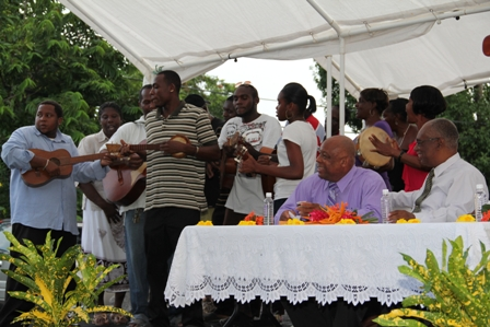 Residents accompanied by the Barnes Ghaut String Band presenting musical gospel renditions while (seated at table L-R) Minister for Social Development on Nevis and Premier and Area Representative Hon. Joseph Parry look on