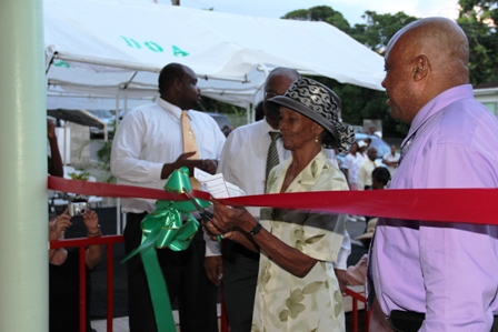 Ms. Eglantine Duberry cuts the ribbon to the new Barnes Ghaut Adult Education Centre with (second from left) Premier of Nevis Hon. Joseph Parry and (R) Minister of Social Development Hon. Hensley Daniel