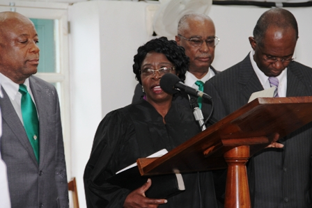 New Speaker of the Nevis Island Assembly takes the oath with Clerk of the House Mr. Dwight Morton. Witnessing the occasion are (back l-r) Deputy Premier Hon. Hensley Daniel and Premier of Nevis Hon Joseph parry)