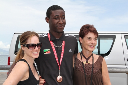 American visitors to Nevis (L-R) Chantal and Maria eager to share the moment with Adrian Williams on his return to Nevis following his bronze medal win at the Commonwealth Youth Games in the Isle of Man