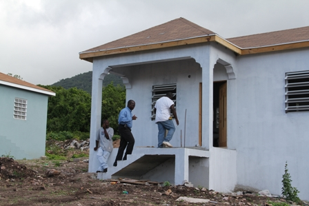 A frontal view of the new Petal design one bedroom home at the Nevis Housing and Land Development Corporation's Sugar Mill Housing Development at Hamilton. The Corporation's Chairman Hon. Robelto Hector accompanying Contractor Mr. Trevor Sutton into the building