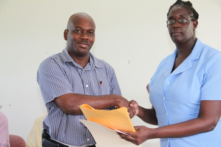 (L-R) President of the New River Farmers Development Cooperative Society Limited Mr. Marcel Hanley received documents from Cooperative Officer in the Department of Cooperatives on Nevis Ms. Alcette Myers