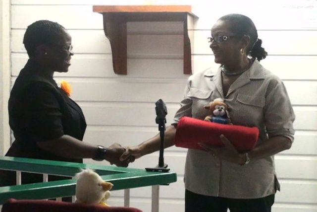 Ms. Jeanette Grell-Hull presents blankets to Project Officer for School Libraries on Nevis, Mrs. Marva Roberts, on behalf of Hearts and Hands for Nevis Incorporated.