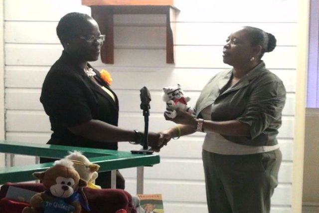Project Officer for School Libraries Mrs. Marva Roberts accepts teddy bears from Mrs. Sonita Daniel on behalf of the Nevis Association of South Florida.
