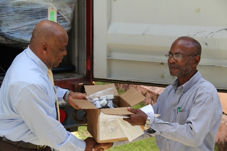 (L-R) Minister of Health in the Nevis Island Administration hands over a box of wound dressing supplies as he hands over the 40 feet container with medical supplies, equipment and furnishings (in the background) to Hospital Administrator Mr. Joe Claxton