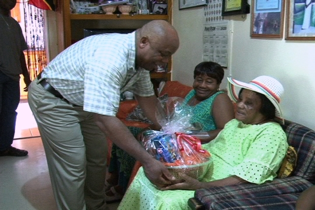 Minister of Social Development in the Nevis Island Administration Hon. Hensley Daniel presents a fruit basket to a senior citizen of Cox Village Mrs. Iris Pinney while one of her daughters Mrs. Icilma Browne looks on For more news out of Nevis visit www.nia.gov.kn your window into Nevis.