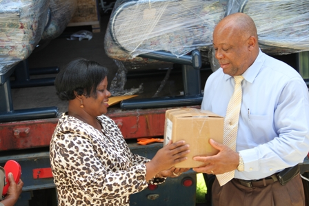 (L-R) Director of the Development Projects Foundation Incorporated Mrs. Myrthlyn Parry hands over a small box of wound dressing supplies from the container of medical supplies (in the background) to Minister of Health Hon. Henslay Daniel for use at the Alexandra Hospital
