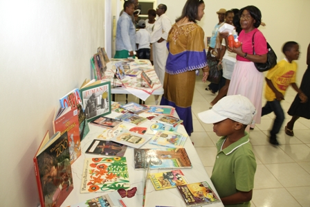 Reading books on display in the new Cotton Ground Community Centre attracts a youngster while villagers tour the facility