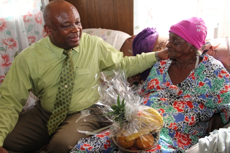 Minister of Social Development, the Ministry responsible for the care and wellbeing of senior citizens on Nevis Hon. Hensley Daniel caringly presents 85-year old Birthday Celebrant Ms. Eulalie Brown with a fruit basket at her home in Brown Hill Village. Prior to taking up residence at Brown Hill Ms. Brown was a long time resident of Brown Pasture Village