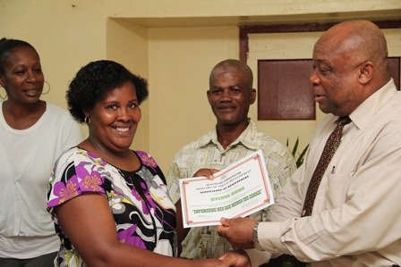 One of three female participates in the Basic Plumbing Installation six week course offered by the Ministry of Social Development Ms. Sylvia Dore of Brown Hill Village receives her Certificate of Achievement from Social Development Minister Hon. Hensley Daniel while (L-R) Events Coordinator in the Ministry of Social Development Ms. Tonya Powell and Course Tutor Mr. Alex Claxton look on