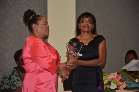 Mrs. Lineth Williams of the Gingerland High School receives plaque from Mrs. Sonita Daniel wife of Deputy Premier Hon. Hensley Daniel