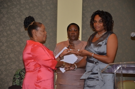 Ms. Tricia Williams of the Gingerland Primary School receives plaque from Mrs. Sonita Daniel wife of Deputy Premier Hon. Hensley Daniel while Principal Education Officer Mrs. Lornette Queeley-Connor looks on