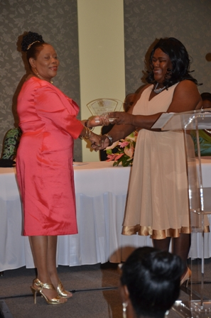 Ms Tanisha Dalton of the Maude Crosse Preparatory School receives plaque from Mrs. Sonita Daniel wife of Deputy Premier Hon. Hensley Daniel