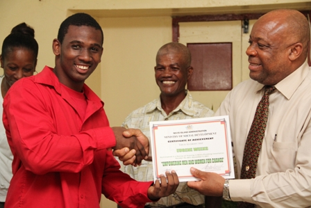 A beaming participant Mr. Eugene Weekes of Hamilton Village receives his Certificate of Achievement from Social Development Minister Hon. Hensley Daniel