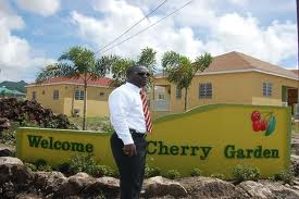 Cherry Gardens Affordable Housing with Director of Land and Housing Mr.Eustace Nisbett standing in front of the property.