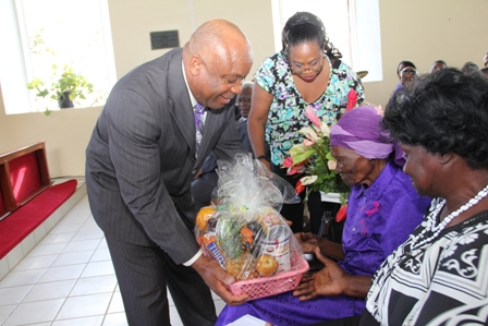 "Minister responsible for the care and development of seniors on Nevis and Deputy Premier Hon. Hensley Daniel presents a food basket and a plaque of recognition from the Social Services Department to Birthday Girl Ms. Celian ""Martin"" Powell on the occasion of her 100th birthday. Looking on are (standing) her oldest grandchild Mrs. Kathleen Rawlins and (seated extreme right) her daughter Mrs. Iris Dolcina Brown"