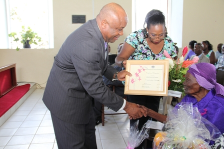 "Minister responsible for the care and development of seniors on Nevis and Deputy Premier Hon. Hensley Daniel presenting the Certificate of recognition from the Social Services Department to Birthday Girl Ms. Celian ""Martin"" Powell on the occasion of her 100th birthday"