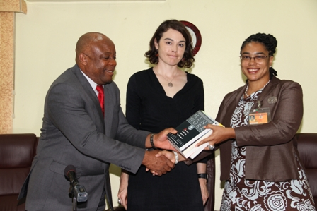 (L-R) Minister for Social Development on Nevis Hon. Hensley Daniel hands over books to Family Services Supervisor/Counsellor Social Services Department on Nevis Mrs. Halima Gresham while (center) Deputy Public Affairs Officer at the Embassy of the United States to Barbados and the Eastern Caribbean Ms. Rachel Zaspel looks on