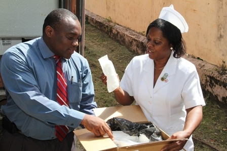 Medical Chief of Staff at the Alexandra Hospital Dr. John Essien and Head Nurse and Matron at the Alexandra Hospital Aldris Dias inspecting one of the many boxes of medical supplies and equipment from the 40ft container