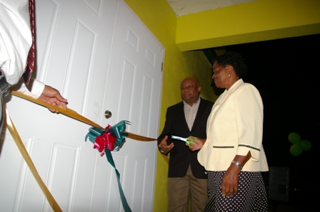 Minister for Social Development on Nevis Hon. Hensley Daniel looks on as Villager Ms. Soreatha Franc cuts the ribbon to the new Fountain Community Centre