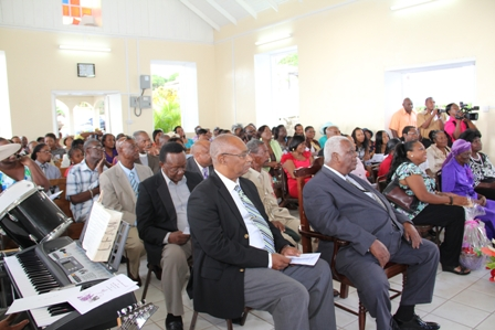 "Front row (L-R) Premier of Nevis Hon Joseph Parry and Governor General of St. Kitts and Nevis His Excellency Sir Cuthbert Sebastian were among those present at the 100th Birthday Celebratory Service for Ms. Celian ""Martin"" Powell on January 19th at the New River Methodist Church"