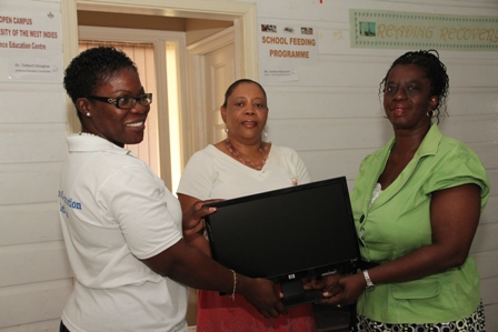 (L-R) Project Officer for School Libraries on Nevis Mrs. Marva Roberts and Director of the Nevis Library Services (NLS) Mrs. Sonita Daniel presenting computer to Teacher Librarian at the Gingerland Secondary School Ms. Londa Browne