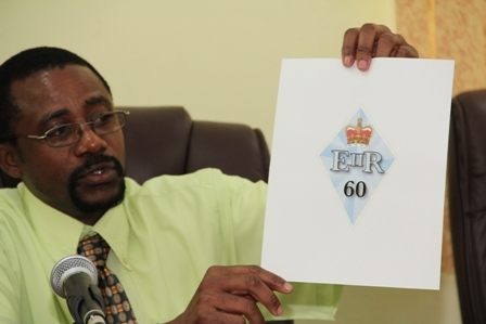 Head of the Nevis Cultural Development Foundation Mr. Chesley Davis presents the proposed logo conceptualised by Rawlins Photo Lab for use during the Queen's anniversary celebrations on Nevis