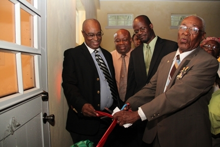 (Extreme right) Renowned Combermere Villager Mr. Franklyn Browne cuts the ribbon at the official opening of the Combermmere Community Centre. Looking on are (L-R) Premier of Nevis hon. Joseph Parry, Minister for Social Development on Nevis Hon. Hensley Daniel Daniel, Area Representative, Attorney General of St. Kitts and Nevis and Federal Minister of Legal Affairs Hon. Patrice Nisbett. Back row (L-R) Minister of Trade on Nevis Hon. Dwight Cozier and a Villager