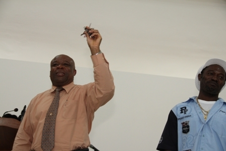 (L-R) Minister for Social Development on Nevis Hon. Hensley Daniel showing keys for the new Combermere Community Centre from Contractor Mr. Livingston Mills