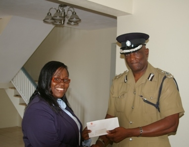 Caribbean Cable Communications Branch Manager-Nevis, Mrs.Trecia Daniel handing over gift of complimentary cable to ACP Robert Liburd