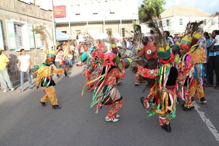 Young Masqueraders dance to the beat of the Big Drum as they entertain those present at the official opening of Tourism Week 2012 in Charlestown