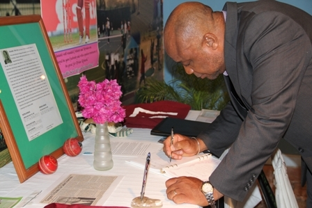 "Deputy Premier and Minister of youth and Sports on Nevis Hon. Hensley Daniel signs the condolence book in memory of Runako Morton. His tribute reads: ""Hensley Daniel – Gone too soon. May flights of Angels sing you to rest"""