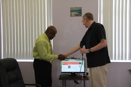 St. Kitts and Nevis Circle of Care representative Mr. Jean Van Eeden handing over lap top computer to Minister of Health and Social Development Hon. Hensley Daniel