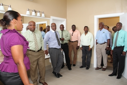 "A section of the touring party enters one of the two large dressing rooms for artists performing at the centre. (L-R) General Manager of the Nevis Performing Arts Centre Mrs. Deslyn Williams-Johnson, Minister of Culture Hon. Hensley Daniel, Premier of Nevis Hon. Joseph Parry, Minister of Communication and Works Hon. Carlisle Powell, Projects Manager of Surrey Paving and Aggregate Mr. Desmond Lewis, Construction Manager of Surrey Paving Mr. Dwight Powell, Projects Director of Surrey Paving Mr. Michael G. Archer, IXI Designs Architect in St. Maarten Mr. John Baker, Special Advisor to Culture Mr. Halsted ""Sooty"" Byron and Cabinet Secretary Mr. Ashley Farrell"