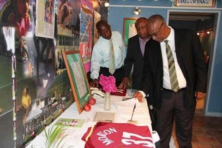"(L-R) Cabinet Secretary in the Nevis Island Administration Mr. Ashley Farrell, Deputy Premier and Minister of Youth and Sports on Nevis Hon. Hensley Daniel and Premier of Nevis Hon. Joseph Parry view the special tribute to Runako Morton at the Sports museum in Charlestown one day ahead of his funeral service on March 17, 2012. Mr. Farrell's tribute read: ""Ashley S. Farrell. Gone too soon, may your legacy live on!"""
