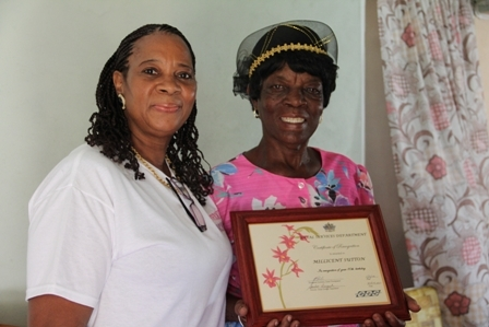 Director of Senior Citizens Division in the Department of Social Services Mrs. Garcia Hendrickson with 80 year old Birthday Girl Mrs. Millicent Sutton at her home in Cotton Ground
