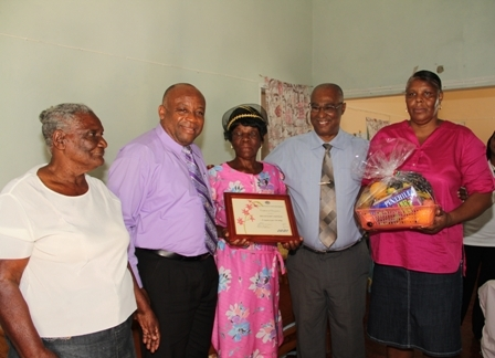 (L-R) Mrs. Millicent Sutton's neighbour Merle, Deputy Premier and Minister of Social Development Hon. Hensley Daniel, birthday Girl Mrs. Millicent Sutton, Premier of Nevis Hon. Joseph Parry and caretaker Portia