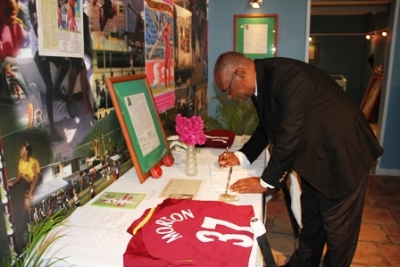 "Premier of Nevis Hon. Joseph Parry signs the condolence book in memory of Nevis' cricket icon Runako Morton at the Sports Museum in Charlestown. His tribute reads: ""Joseph W. Parry Premier – May the love of God embrace him"""