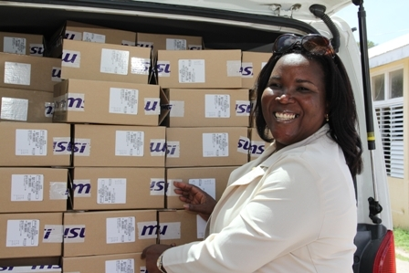 Acting Permanent Secretary in the Ministry of Education and Library Services and Principal Education Officer Mrs. Lornette Queeley-Connor with one of the two busloads of computers for students on Nevis