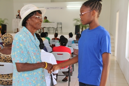 "Nevisian lass Ms. Ercha Stapleton (r) interacts with her senior Mrs. Oretha ""Lizzie"" Wilkerson a member of the St. Johns Mothers Union at International Women's Day celebrations at the Cotton Ground Community Centre on Nevis"