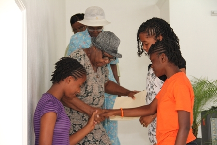 Young girls at the International Women's Day celebrations on Nevis assist members of the St. Johns Mothers Union after rendering a song on stage