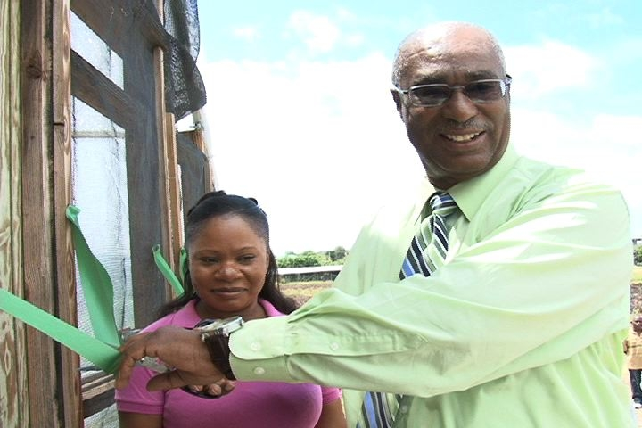 Premier of Nevis, Hon. Joseph Parry,cutting the ribbon to the Green House with Agriculture officer, Miss. Junella Burke looking on