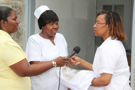 Nevisian Mrs. Marilyn Walters-Drew (r) hands over gift to Nurse Adrienne Ward for patients of the Alexandra Hospital and residents of the Flamboyant Nursing Home on Nevis. Hospital Administrator Ms. Grace Elliott (extreme left) looks on